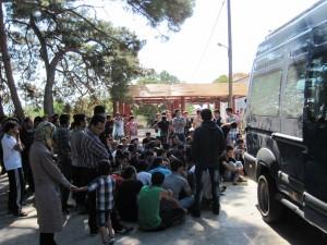 Flüchtlinge warten darauf, photographiert und dann nach Moria gebracht zu werden.