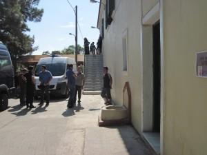 Ein Polizist photographiert einen Flüchtling, bevor er nach Moria gebracht wird.
